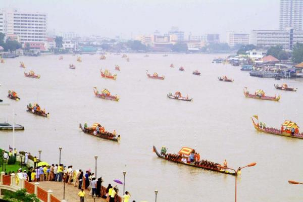 Aerial view of the Royal Barge Processional on the wide Chao Phraya River. The formation stretches to the horizon.