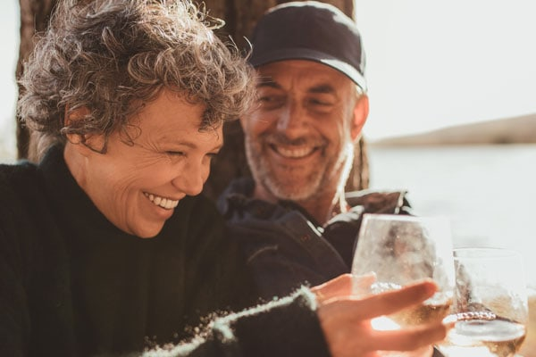 mature couple enjoying drinks on the beach