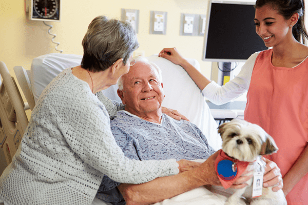 elderly couple smiling at each other while in a hospital room