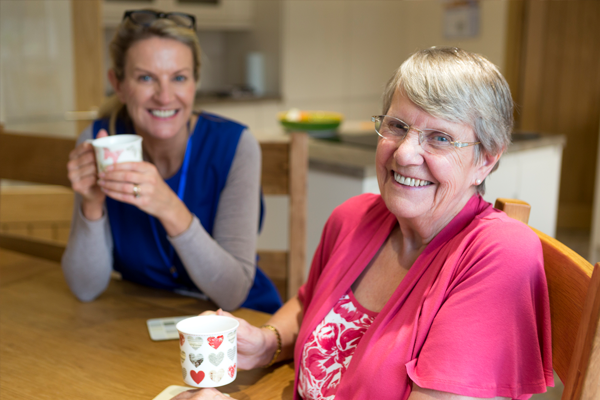 nurse and patient with coffee smiling at the camera