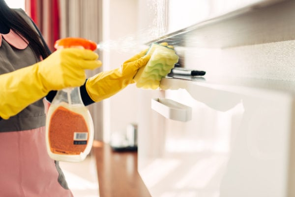 Housemaid hands in gloves cleans furniture with a cleaning spray, hotel room interior on background. Professional housekeeping, charwoman