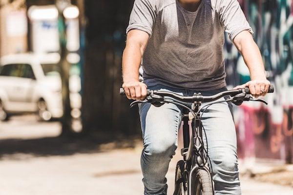 A man grips handlebars as he rides a bike