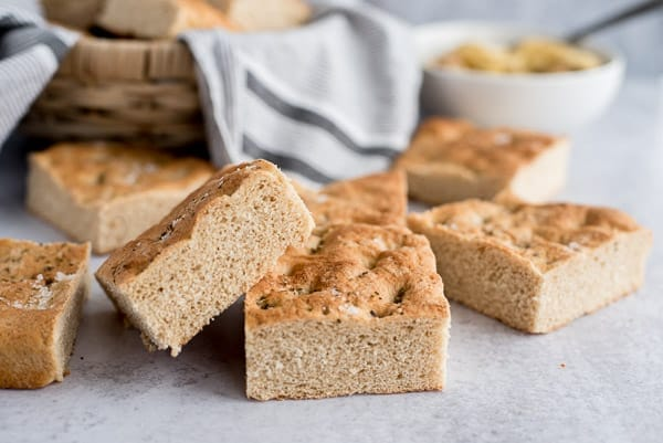 whole wheat focaccia bread stacked by a basket