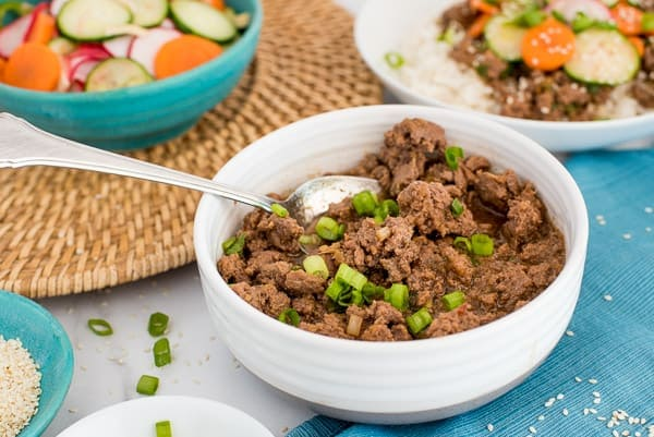 Korean Beef in a white bowl with a bowl of carrots, cucumbers, and radishes near by.
