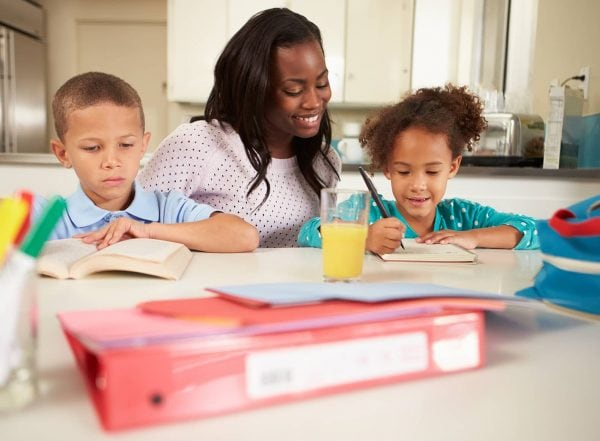 mother sitting at table with her children doing homework