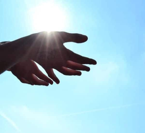 an image of a pair of hands reaching out from the sky. featured image for Inspiring Story of Treasured Memories