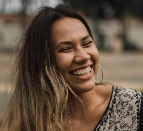 an image of a woman laughing wearing a green and brown shirt. featured image for What Does the Bible Say About Laughter?