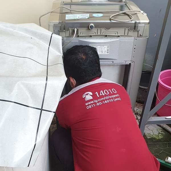 teknisi mesin cuci LG sedang membongkar mesin cuci