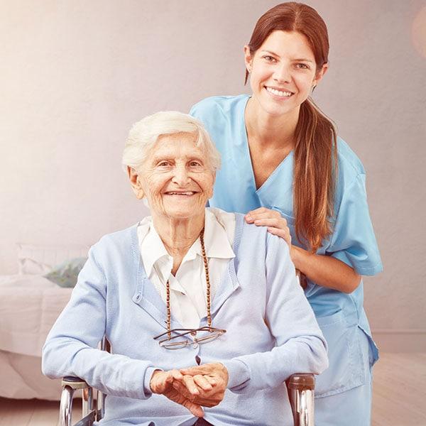 Junge Pflegerin und Seniorin posieren freundlich