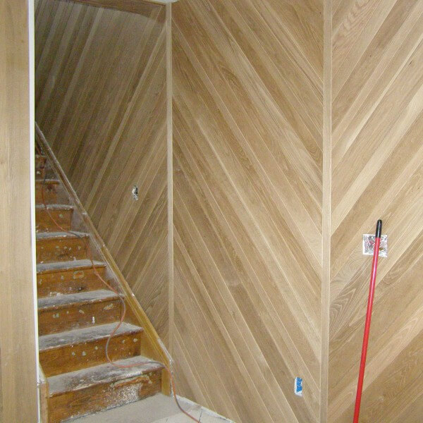 Custom built stair wall wood in a chevron pattern in remodel of basement stairs room in Denver