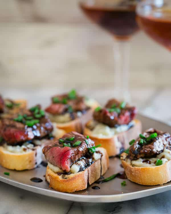 These blue cheese steak crostini are the perfect little appetizer bite. Garlicky toasted bread topped with salty blue cheese, rare steak and a balsamic reduction are a great Valentine's Day nibble.