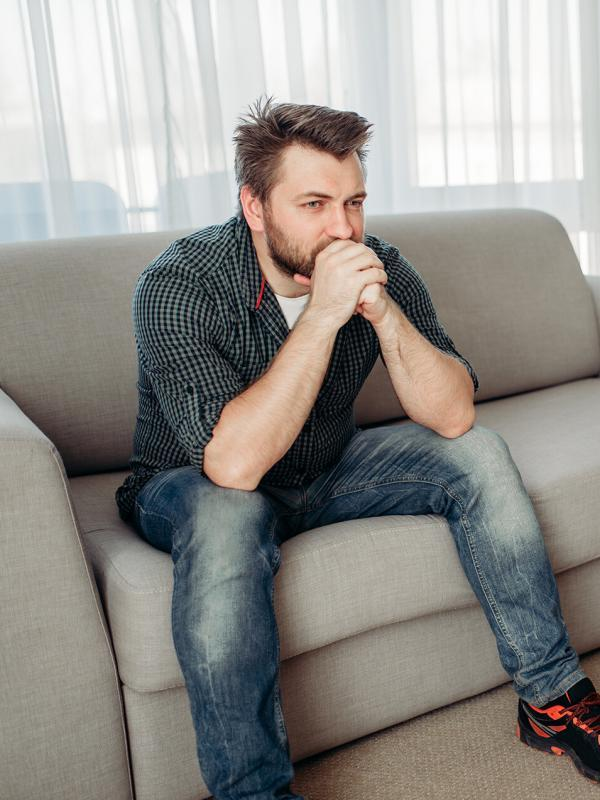 Sad male patient at psychologist, professional psychology support. Female doctor writes notes in notepad, man sitting on sofa