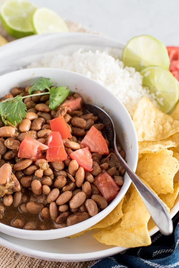 Instant Pot pinto beans in a white bowl with tomatoes on top