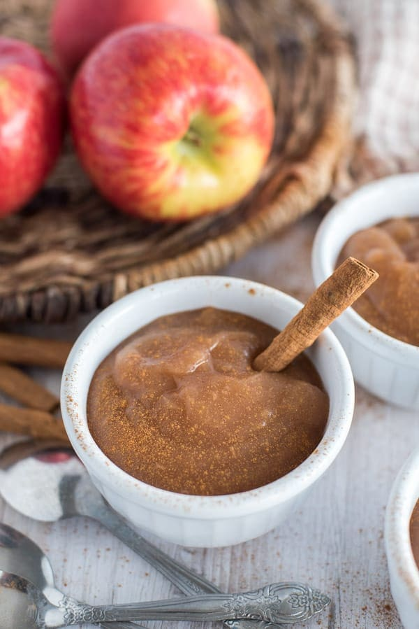 applesauce in white cups with apples and cinnamon sticks in the background