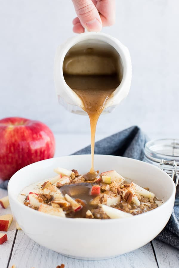 syrup pouring over a white bowl of apple oatmeal