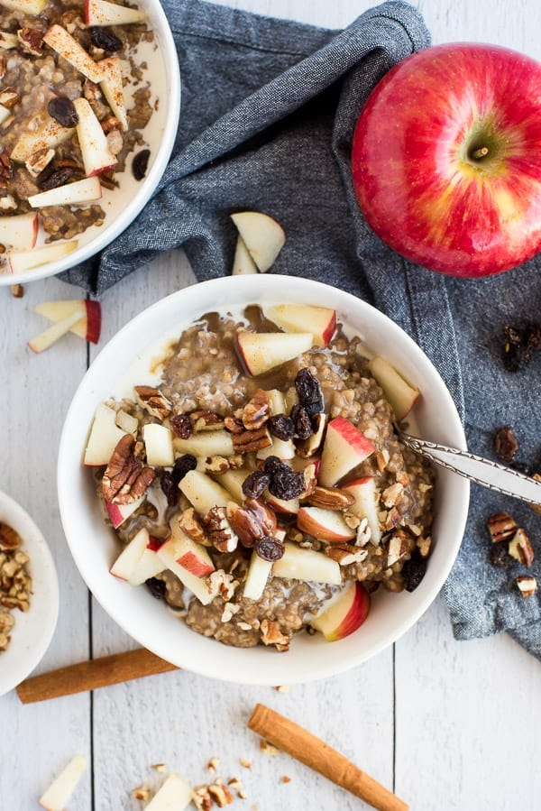 white bowl of steel cut oats with apples cinnamon and syrup