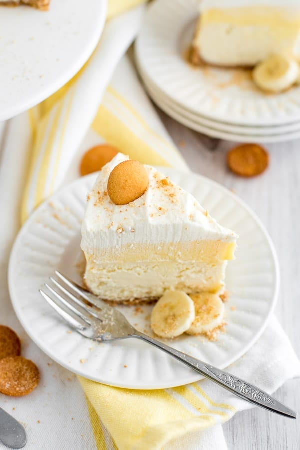 slice of Banana cream pie cheesecake on a white plate with yellow napkins