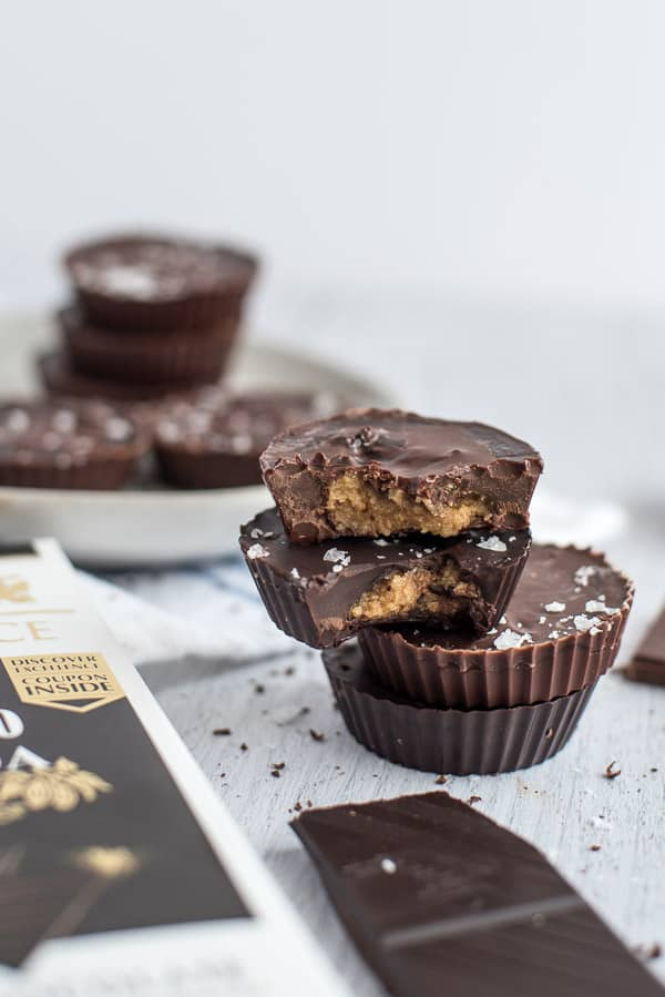Chocolate peanut butter cups stacked on top of each other on a white surface and a candy bar