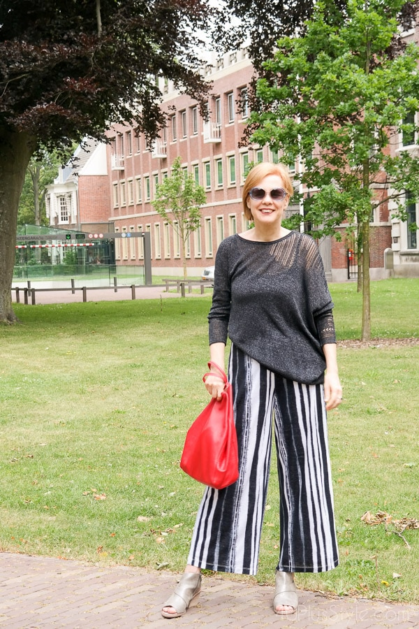 Striped pants with and asymmetrical top make a stylish look! | 40plusstyle.com