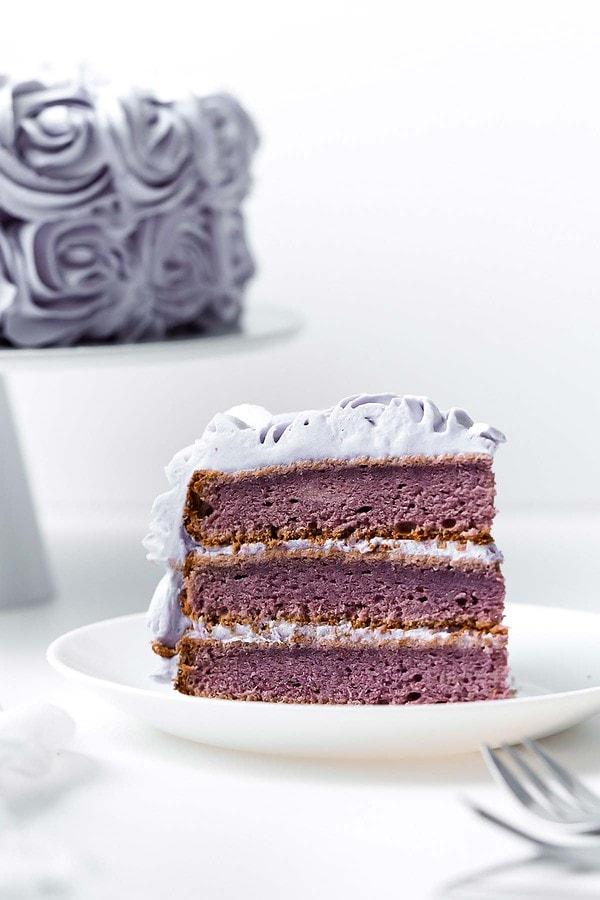 Purple yam cake slice on small white plate
