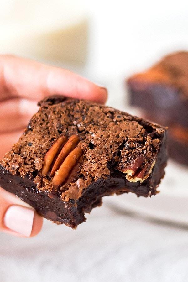 Hand holding bitten brownie
