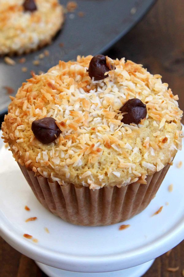 Almond butter muffin with shredded coconut topping on small white stand