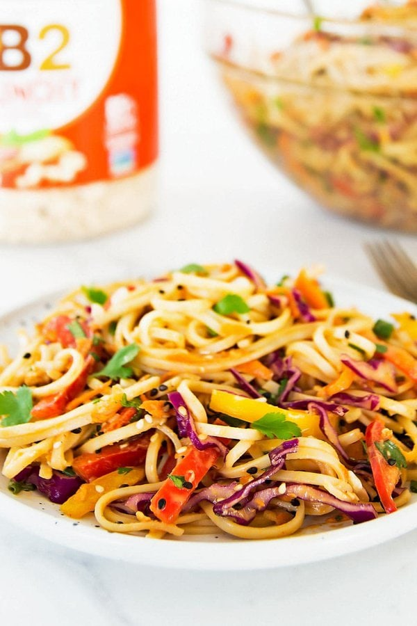 Cold noodle salad with peanut dressing on plate. Bowl and peanut powder in background