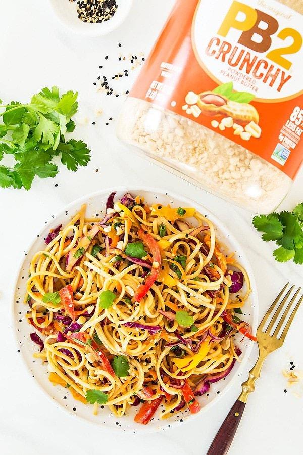 Thai Peanut Noodle salad on plate with fork, cilantro leaves, PB2 powder around plate