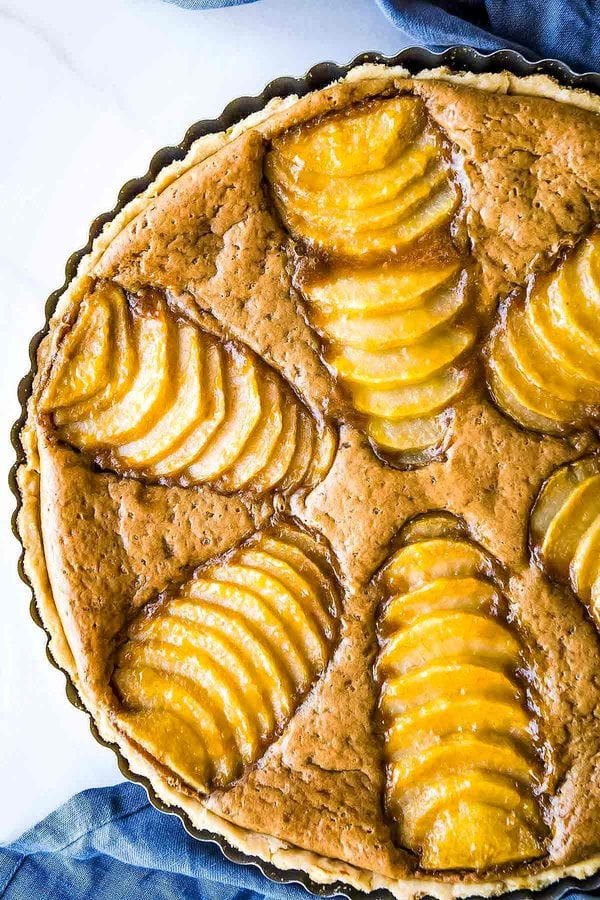 Whole Pear Almond Tart in pan with blue linen cloth