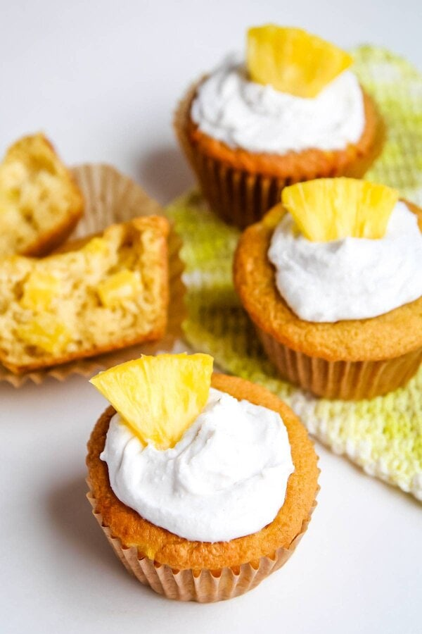 Gluten free pineapple muffins with cross-cut section in background
