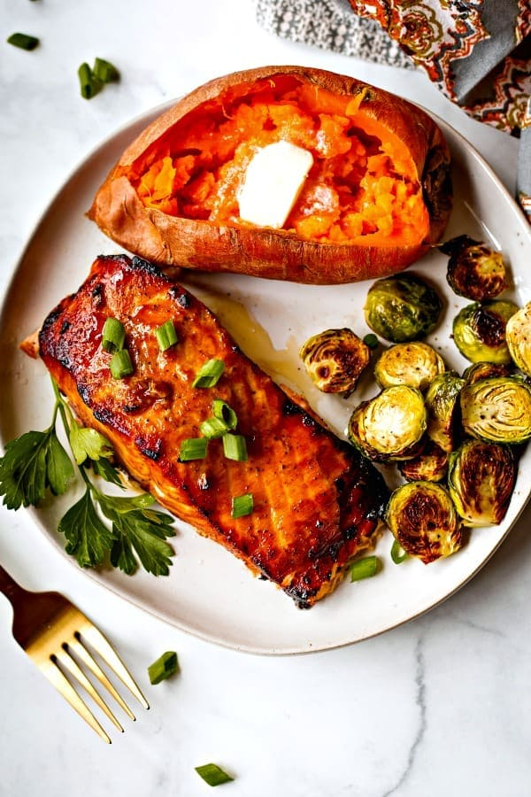 Grilled salmon on a white plate with baked sweet potato