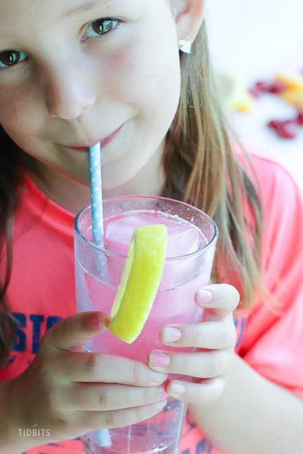A girl drinking fizzy drink from a straw