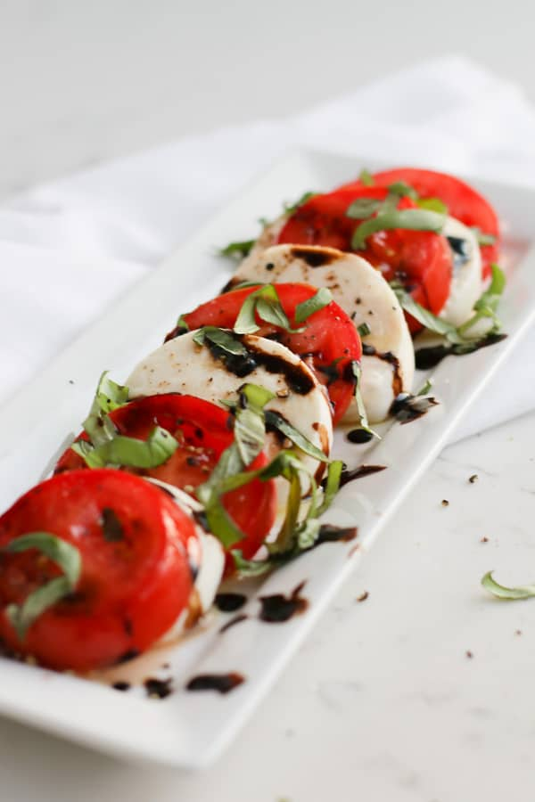Pressuer cooker mozzarella on a white serving plate with tomatoes and balsamic dressing