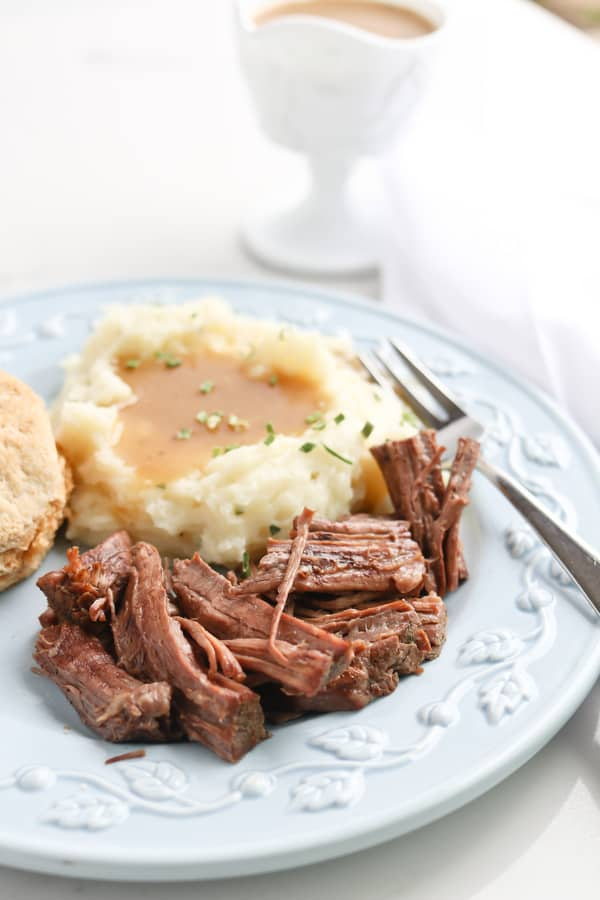 Instant Pot Pot Roast on plate with mashed potato and biscuit