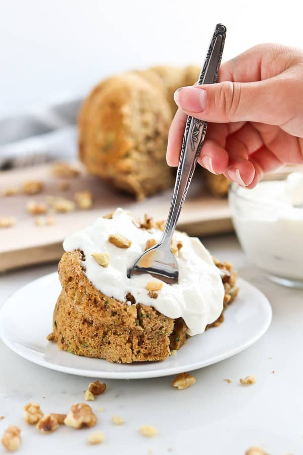 zucchini bread with yogurt sauce on a plate with a fork