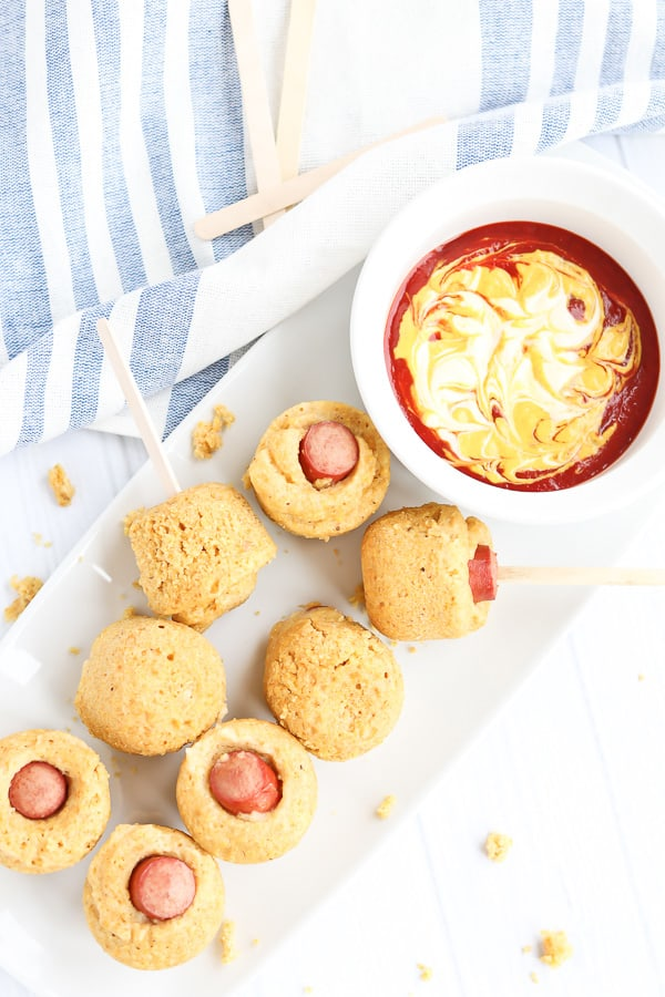 Corn dog muffins on a white platter with ketchup and mustard dip