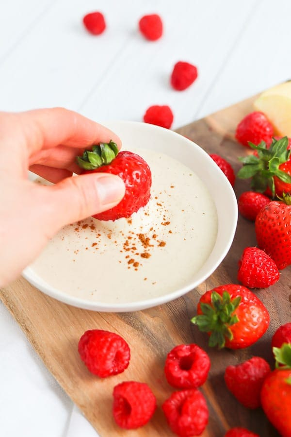 Strawberries and raspberries next to a white bowl of fruit dip
