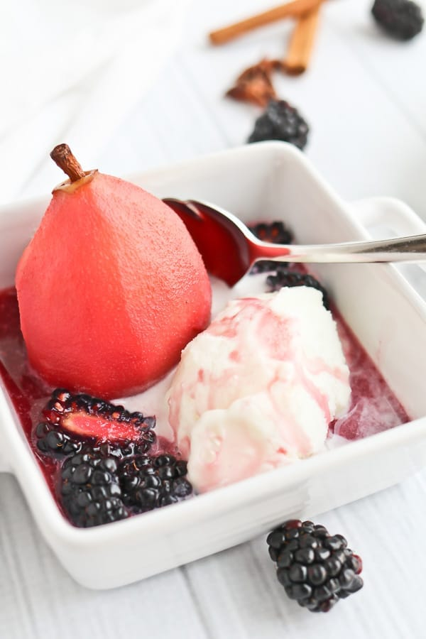 Poached pear in a white bowl with ice cream