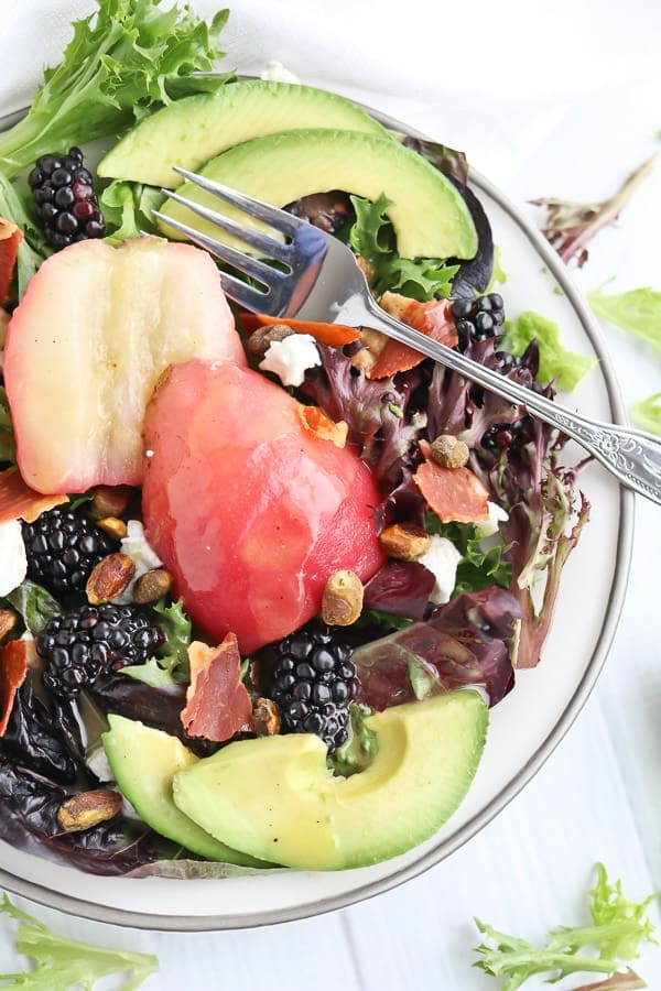 Green salad with poached pears on top