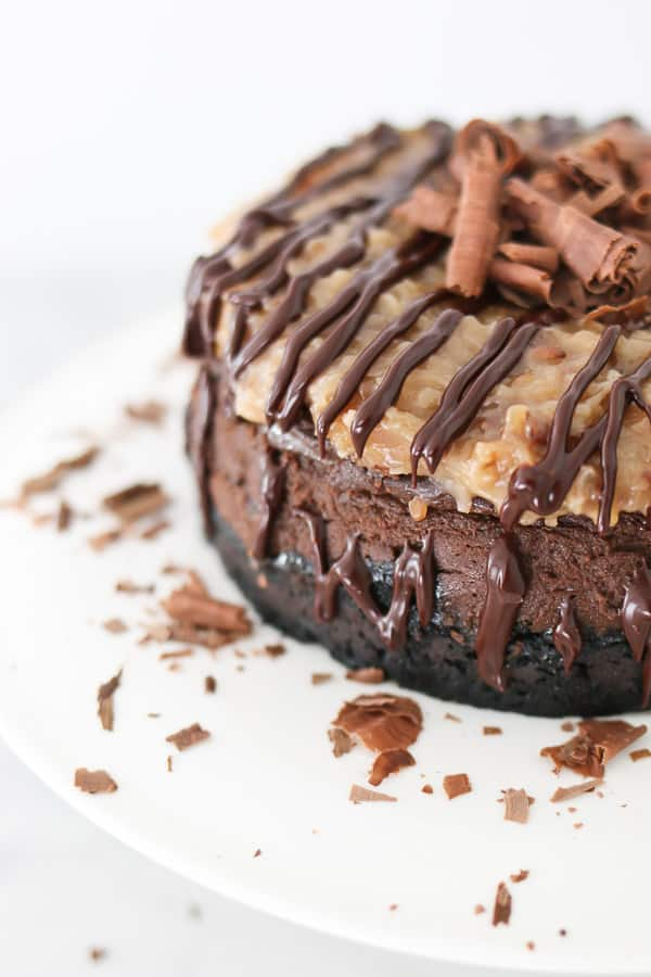 Instant Pot German Chocolate Cheesecake on a white plate with chocolate drizzle