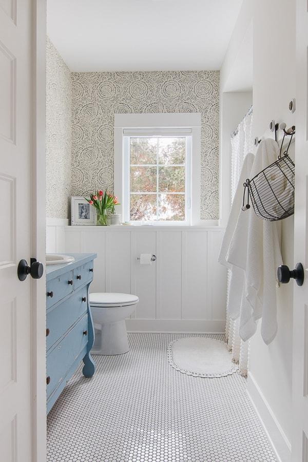 floral blue wallpaper blue vintage vanity and white penny tile bathroom