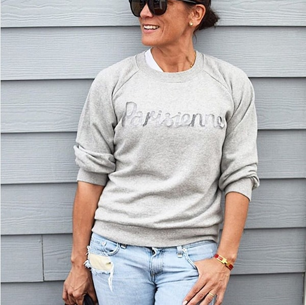 Casual outfit idea for women over 40: Gray sweater and bleached jeans | 40plusstyle.com