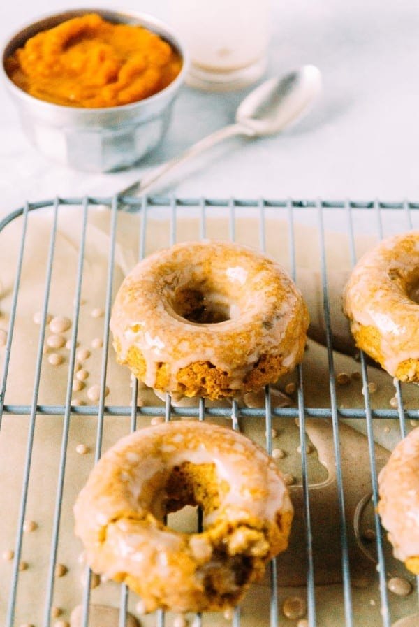 Vegan Pumpkin Doughnuts are perfect for the cozy fall season! Topped with a cinnamon maple vegan frosting and ready for your next breakfast.