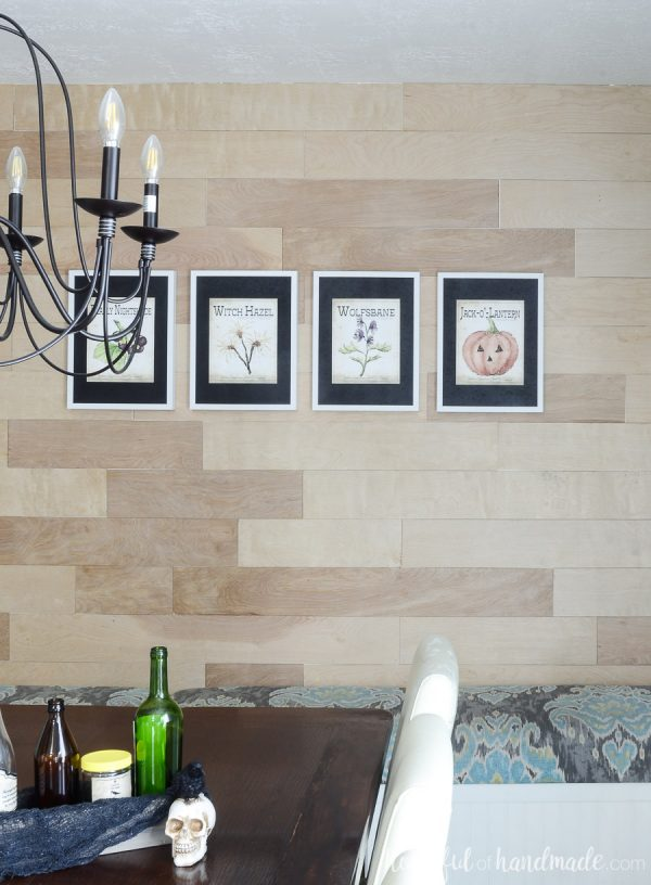Printable Halloween art in white frames with black mats. Hanging on a wood plank wall in the dining room.