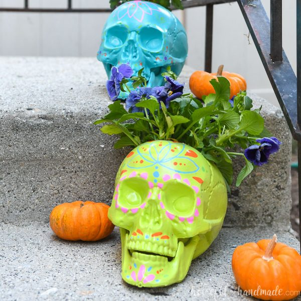 Porch with 2 DIY sugar skull planters on it with fall flowers in them.