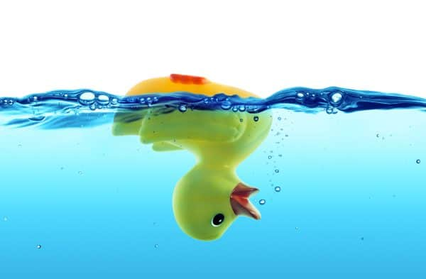 Upside down rubber duck floating in water signifying being underwater due to lack of child support payments