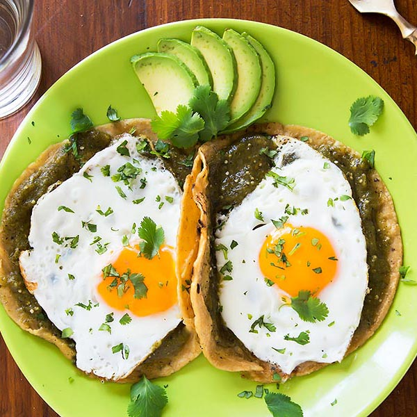 Plate of eggs on tortillas with salsa verde