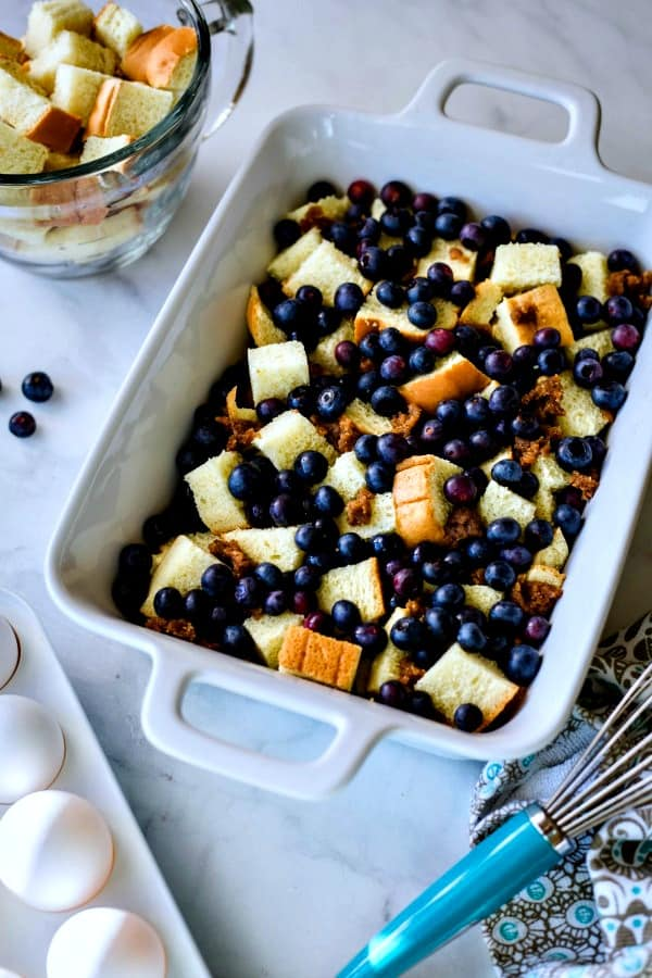 white casserole dish with bread cubes and fresh blueberries being prepped for a Blueberry Strata casserole