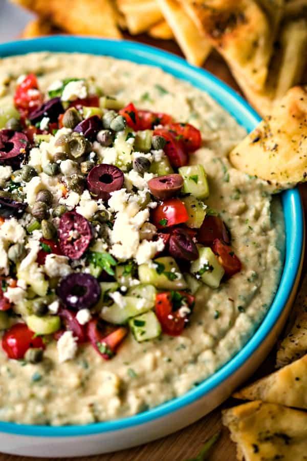 Mediterranean Layered Dip of white bean hummus and pico on a blue plate