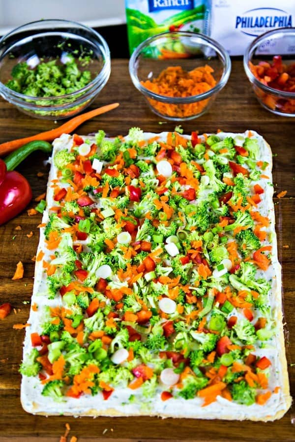baked crescent dough with ranch cream cheese and chopped veggies on a wooden board